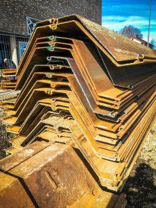 For å kunne gjennomføre gravearbeidene i Skårersletta på en sikker måte, må vi stabilisere grunnen med spunt. Spunt er lange stålplater som vibreres ned i bakken. Foto: Lørenskog kommune.
